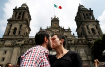 A couple kiss each other in front of the cathedral during a march in support of gay marriage, sexual and gender diversity in Mexico City, Mexico on September 11, 2016. There have been counter-demonstrations, against same-sex marriage, held in Mexican citi