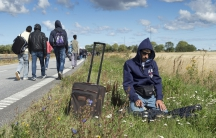 A migrant prays beside a freeway north of Rodby as a large group of migrants, mainly from Syria, walk on the highway towards the north September 7, 2015. Many migrants, mainly from Syria and Iraq, have arrived in Denmark over the last few days.
