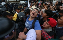 Demonstrators clash with riot police as they take part during a march demanding the resignation of President Enrique Pena Nieto in downtown Mexico City, Mexico, September 15, 2016.