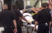 A policeman takes a photo of a man they identify as Ahmad Khan Rahami, who is wanted for questioning in connection with an explosion in New York City, as he is placed into an ambulance in Linden, New Jersey, in this still image taken from video.