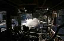 Aleppo residents walk past a burnt bus in the city's rebel-held Seif al-Dawla neighborhood.