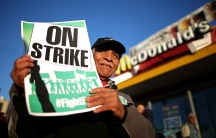 Man holding up protest sign in front of a McDonald's