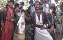 Yemenis pose for a picture next to a part of a missile they say was dropped during a Saudi-led air strike near the northwestern city of Saada, Yemen