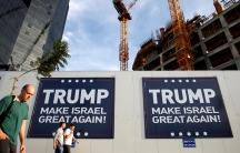People walk past signs bearing the name of U.S. President-elect Republican Donald Trump in Tel Aviv, Israel on November 14, 2016.