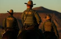 Men on horses in Border Patrol uniforms, seen from back at dusk