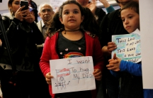 "Young girl holding sign in front of crowd, ""I want to hug my dad"""