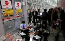 Women walk by a team of volunteer lawyers in their makeshift office working to assist travelers detained as part of Donald Trump's travel ban in Terminal 4 at John F. Kennedy International Airport in Queens.