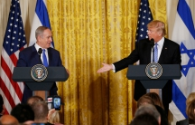 US President Donald Trump (right) reaches to greet Israeli Prime Minister Benjamin Netanyahu after a joint news conference at the White House in Washington, DC, on February 15, 2017.