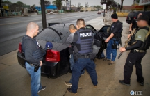 ICE officers detain a suspect as they conduct a targeted enforcement operation in Los Angeles.