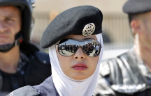 A Jordanian police woman stands guard in front of the U.S. embassy in Amman August 31, 2013.