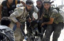 Free Syrian Army fighters carry a fellow fighter after he was wounded on the front line in Aleppo's Sheikh Saeed neighbourhood, September 21, 2013.