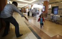 Four year old Portia Walton runs toward Abdul Haji during the Westgate Mall massacre. Her mom and others shelter under the black and white table in the middle. The terrorists are holed up and firing from the supermarket beyond the table.