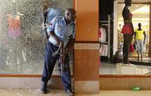 A Kenyan police officer tries to secure an area inside the Westgate Shopping Centre after a militant siege.