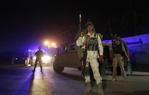 Afghan policemen keep watch at the site of an attack in Kabul.