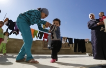 A Syrian refugee girl helps her brother walk