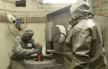 Workers dressed in protective clothes hold a mock chemical World War Two grenade during a demonstration