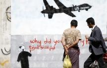 Men look at wall graffiti depicting a American drone along a street in Sana'a, Yemen, on November 9, 2013.