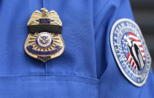 A TSA agent wears a black ribbon over his badge during a memorial service for a slain colleague.