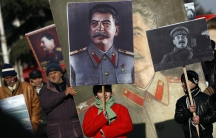 People carry portraits of late Soviet dictator Josef Stalin as they attend a gathering marking the 130th anniversary of his birthday