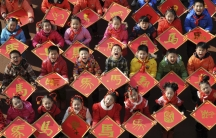 """Children pose with their paper-cut works of the Chinese character for """"horse"""", ahead of the Year of the Horse in Chinese zodiac, at a primary school in Jiujiang, Jiangxi province, December 31, 2013."""