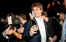 Norwegian chess world champion Magnus Carlsen in a suit and holding a bottle a Champagne  while attending the Norwegian Sports Gala in Oslo January 4, 2014.