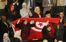 Members of the Tunisian parliament wave flags after approving the country's new constitution.. Tunisia's national assembly approved the country's new constitution on Sunday in one of the final steps to full democracy three years after protests erupted int