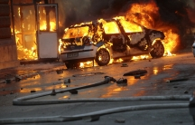 A car burns as anti-government protesters clash with police in Sarajevo.