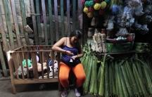 A woman sells banana leaves at a market in Managua, Nicaragua.
