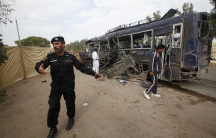 A security official prevents members of the media from approaching a damaged police bus at the site of an explosion in Karachi targeting policemen on February 13, 2014.