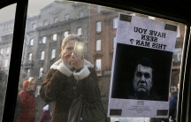 """A woman takes photos of a """"Wanted"""" notice for fugitive Ukrainian President Victor Yanukovich, plastered on the window of a car used as a barricade, near Kiev's Independent Square February 24, 2014."""
