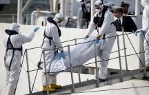 Italian coastguard personnel in protective clothing carry the body of a dead immigrant off their ship, Bruno Gregoretti, in the Grand Harbor of Valletta, Malta, on April 20, 2015.