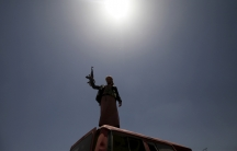 A follower of the Houthi group raises his weapon as he stands on a vehicle on a damaged street in Sanaa on April 21, 2015.