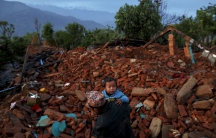A villager carries a child amid debris in Gorkha, Nepal, following the earthquake that struck Nepal on April 25, 2015.