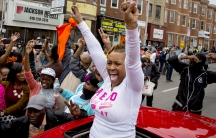 Baltimore residents gather at the corner North and Pennsylvania Avenues on May 1, 2015 to cheer the news that six police officer will face charges in the death of Freddie Gray.
