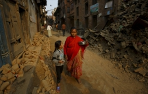 A woman and a child, returning from a temple, walk past damaged and collapsed houses following the April 25, 2015, earthquake in Nepal.