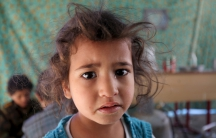 An internally displaced girl waits for her turn to receive food at a school in Sanaa May 17, 2015. Residents were forced to leave their homes in the nearby province of Saada amidst Saudi-led air strikes.