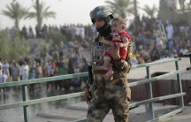 An Iraqi soldier carries a displaced child from Ramadi on the outskirts of Baghdad on May 19, 2015.