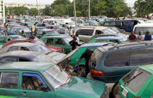 A man works on the engine of his car, as motorists wait for fuel at a gas station in Abuja.