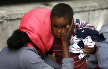 A mother embraces her child next to the Tiburtina train station in Rome.