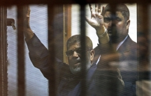 Deposed Egyptian President Mohamed Morsi greets his lawyers and people from behind bars after his verdict at a court on the outskirts of Cairo, Egypt on June 16, 2015.