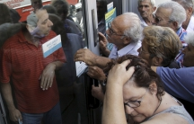Pensioners waiting outside a closed National Bank branch and hoping to get their pensions, argue with a bank employee (L) in Iraklio on the island of Crete, Greece June 29, 2015. Greeks struggled to adjust to shuttered banks, closed cash machines and a cl