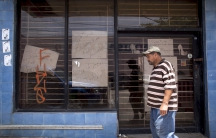 "A man walks past a closed store with signs reading ""Closing down sale"" and ""Everything goes, shoes, clothes, take advantage"" in Arecibo, Puerto Rico, June 29, 2015."