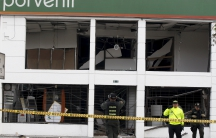 Police examine a bombed-out office in Bogota's financial district