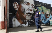 A security guard walks past a wall mural depicting President Barack Obama in Kenya's capital, Nairobi