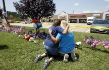 Betty Maynard (L) hugs her friend Cindy Atterton beside a growing memorial at the Armed Forces Career Center in Chattanooga, Tennessee July 17, 2015. Four U.S. Marines were killed on Thursday by a suspected gunman the FBI has confirmed as Mohammod Youssuf