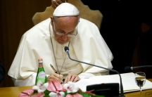 """Pope Francis signs a declaration during the """"Modern Slavery and Climate Change"""" conference"""