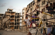 Palestinian children play on a ferris wheel near residential buildings that witnesses said were destroyed by Israeli shelling during a 50-day war in the summer of 2014, in Beit Lahiya town in the northern Gaza, July 27, 2015.