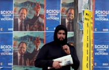A man stands at a bus stop in front of campaign posters advertising Buenos Aires' province governor and presidential candidate Daniel Scioli, ahead of August 9 party primary elections
