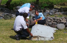 French gendarmes and police inspect a piece of plane debris found on a beach on the French Indian Ocean island of La Reunion.