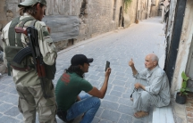 Free Syrian Army fighters snap a picture of an elderly man using a mobile phone in Old Aleppo, Syria.